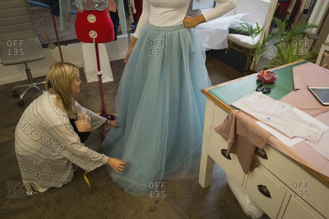 Fashion designer dressing customer in fashion studio