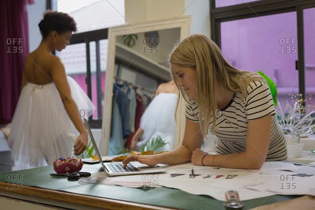 Beautiful fashion designer using laptop in fashion studio