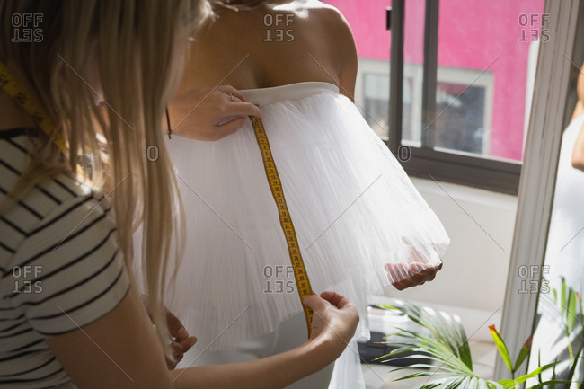 Fashion designer taking measurement of customer in fitness studio
