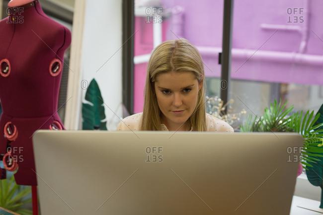 Beautiful fashion designer using computer in fashion studio