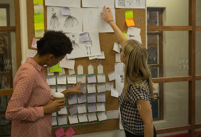 Fashion designer discussing on sticky note in fashion studio