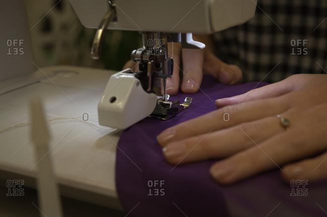 Close-up of fashion designer using sewing machine in fashion studio
