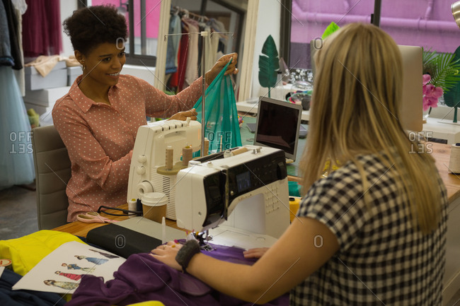 Fashion designers using sewing machine in fashion studio