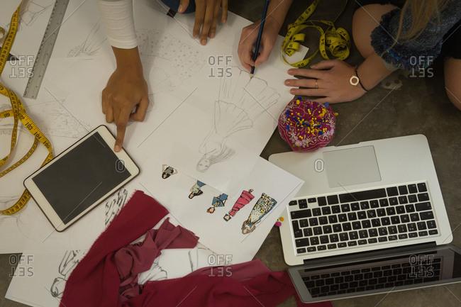 Fashion designers drawing a sketch using digital tablet in fashion studio