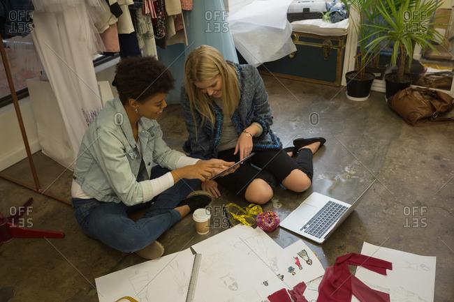 Fashion designer using digital tablet in fashion studio