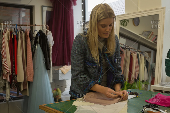 Beautiful fashion designer pinning on fabric in fashion studio