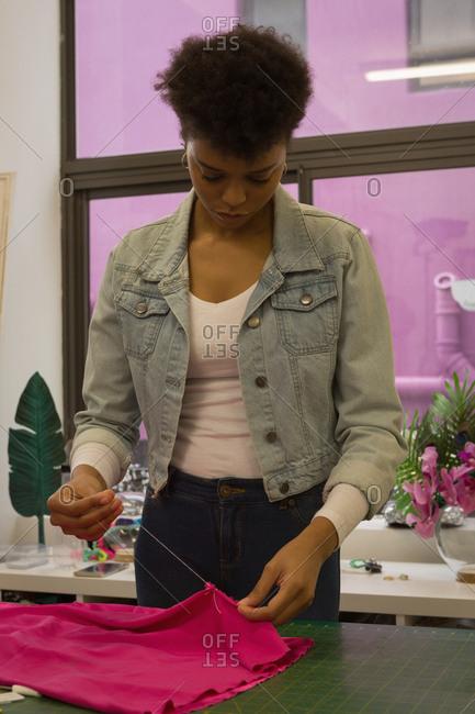 Fashion designer sewing by hand in fashion studio