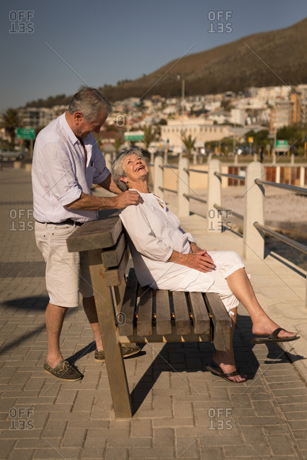Smiling senior couple embracing near sea side at promenade