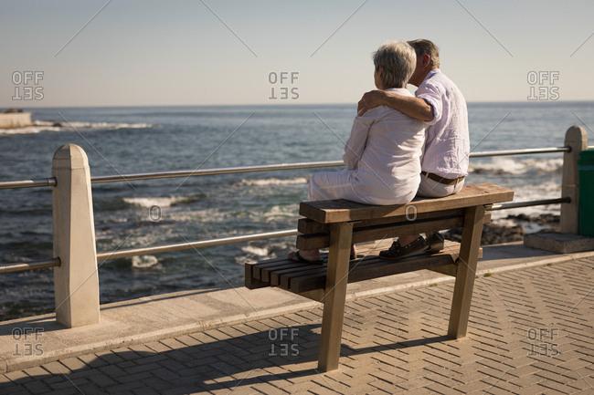 Senior couple sitting on bench near sea side at promenade