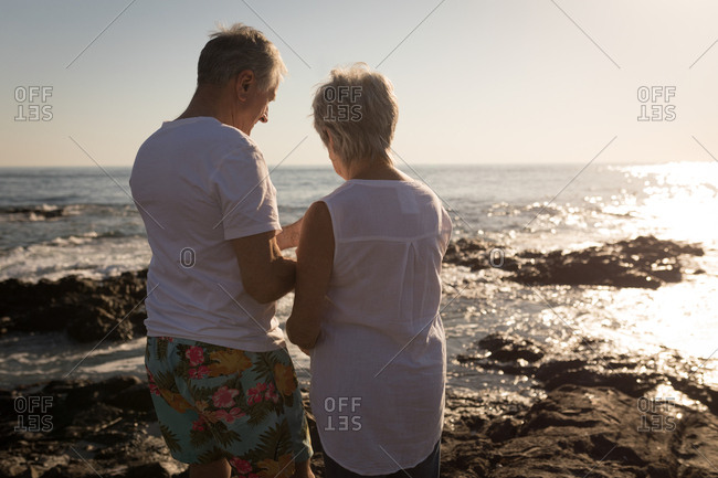 Rear view of senior couple standing near sea side on a sunny day