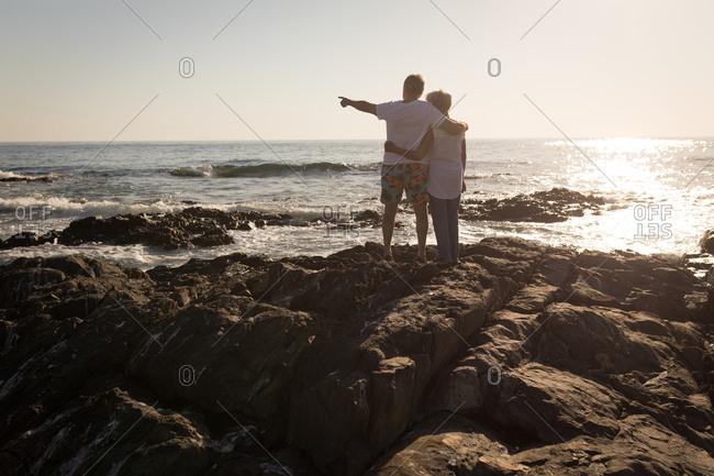 Rear view of senior man standing on rock near sea side