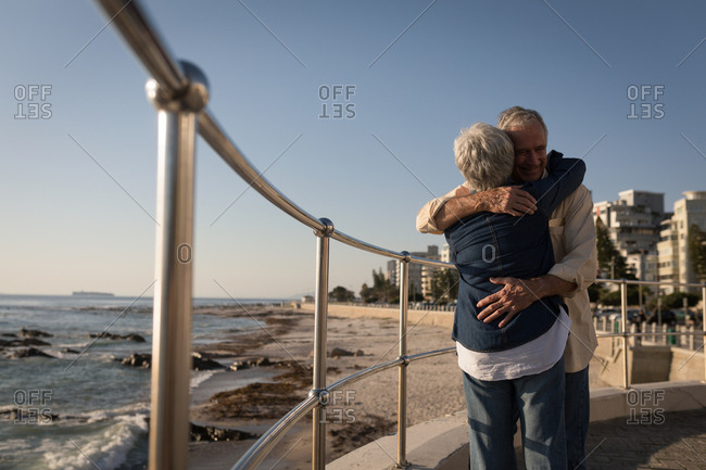 Senior couple embracing each other near sea side at promenade on a sunny day