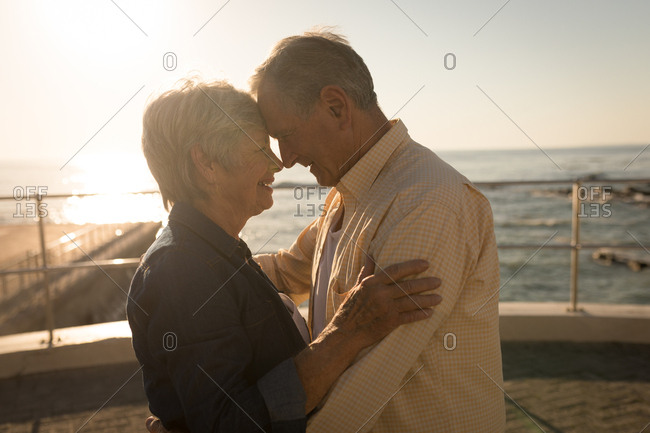 Romantic senior couple standing at promenade on a sunny day