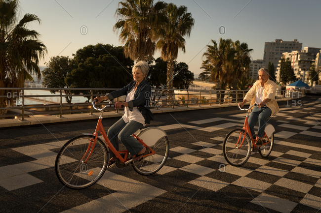 Senior couple riding bicycle at promenade on a sunny day