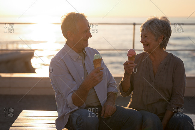 Happy senior couple having ice cream at promenade