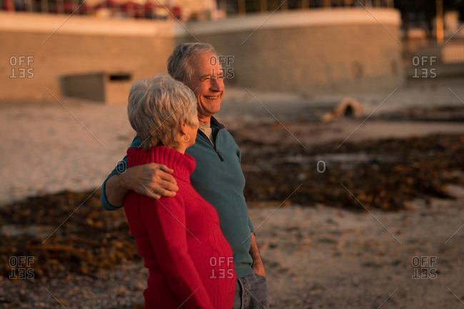 Senior couple talking on beach during sunset