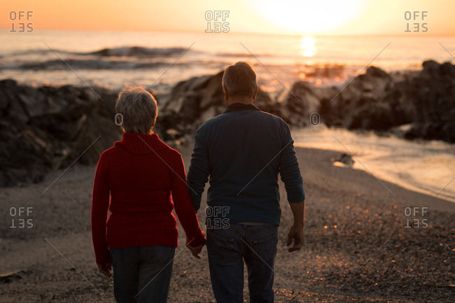 Rear view of senior couple walking on beach during sunset