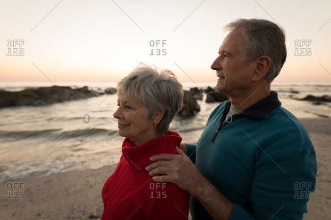 Close-up of senior couple standing on beach during sunset