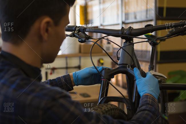 Rear view of man repairing bicycle shock absorber in shop