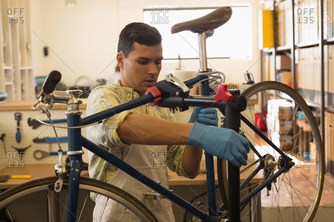 Man mounting bicycle on repair stand in workshop