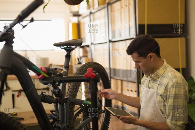 Man using digital tablet while repairing bicycle in workshop