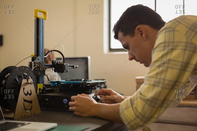 Mechanic using die machine on table in workshop