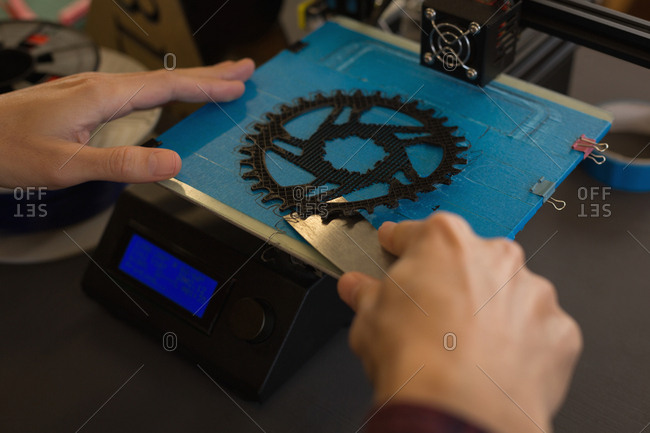 Close-up of mechanic taking out chain ring from die machine on workshop