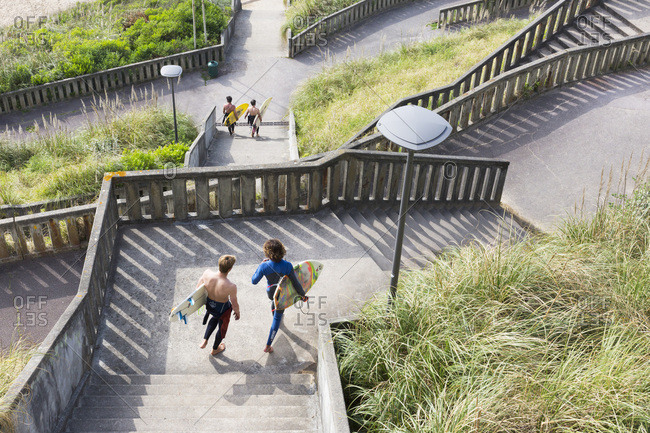 May 22, 2018: Surfers heading to down stairways leading to Plage de la Cote de Basques and Plage Marbella