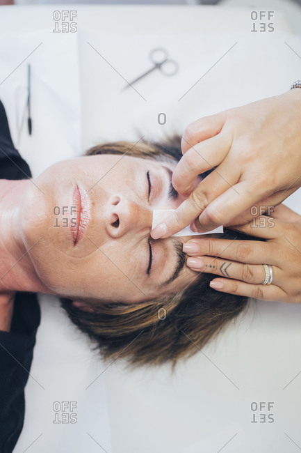 Beautician removing facial hair on a customer