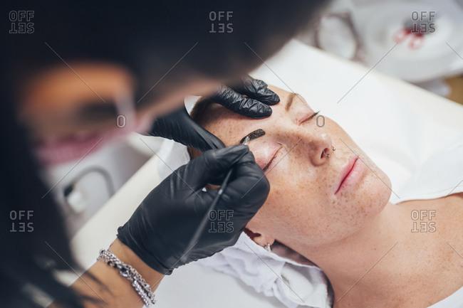 Beautician working on a customer's eyebrow