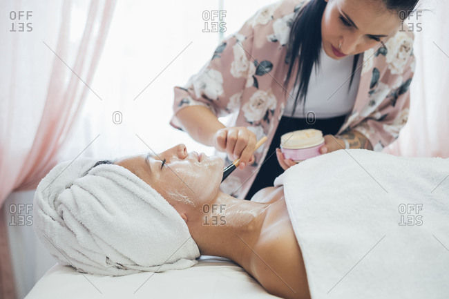Beautician applying face mask on a customer