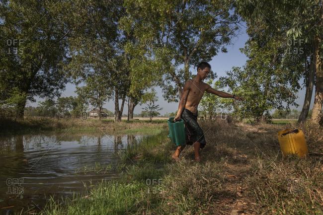Pathein, Myanmar - Feb 4,2014: A man carries a bucket of water in rural setting