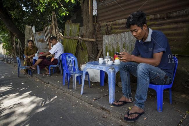 Yangon, Myanmar - Feb 13, 2017: Person on their cell phone on a sidewalk in Myanmar