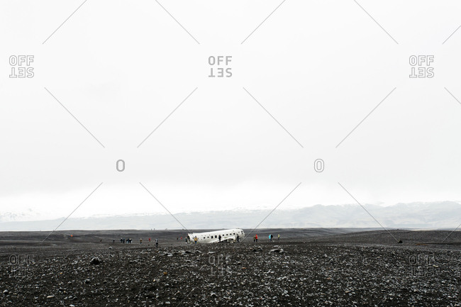 Unrecognizable people by plane wreck in Solheimasandur Iceland