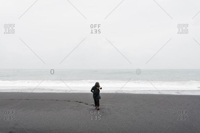 Woman walking on black sand beach near Vik, Iceland