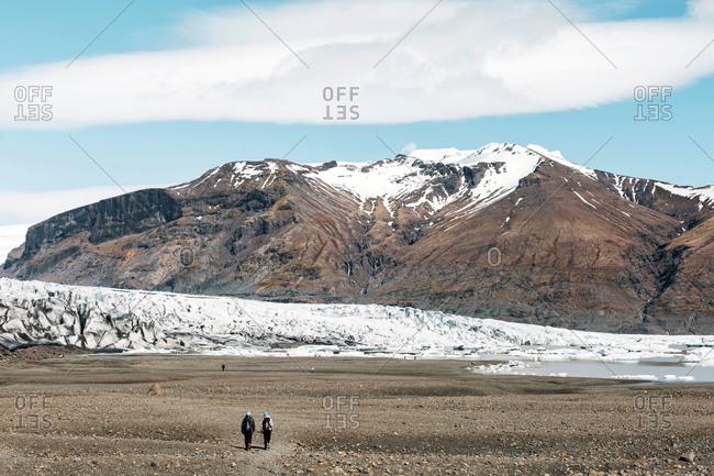 Couple hiking by Svinafellsjokull Glacier at Skaftafell National Park