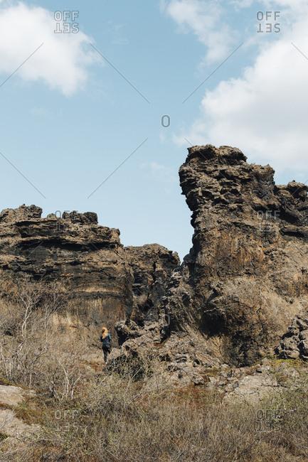 Woman hiking by rock formation at Dimmuborgir lava fields