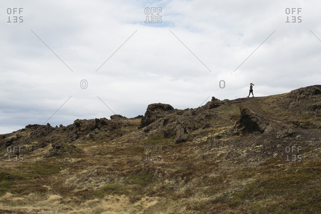 Woman hiking by Myvatn volcanic lake in northern Iceland