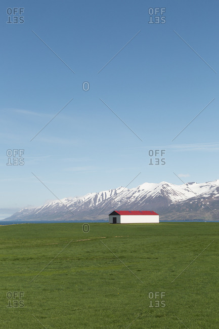 Barn by Snowy mountains in north fjords Iceland