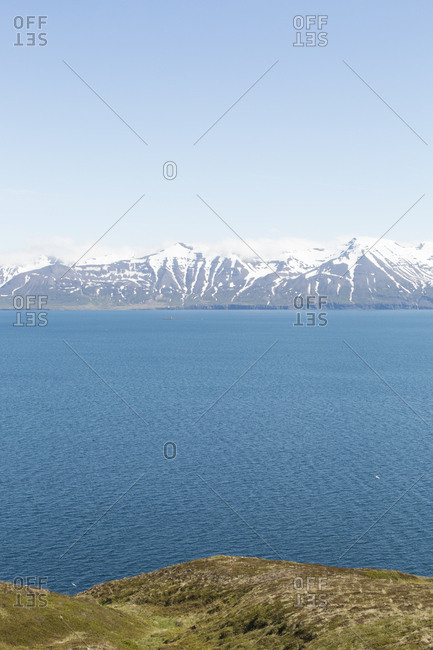 Snowy mountains over ocean by North fjords Iceland