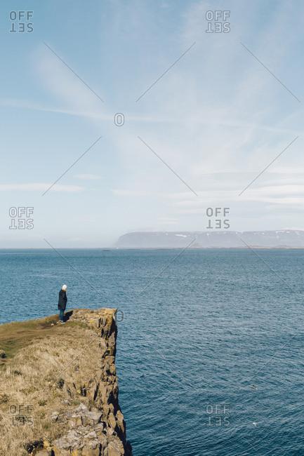 Woman watching the ocean by Stykkisholmur town in west Iceland