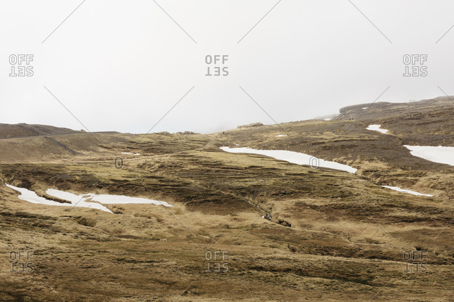 Snow and moss on mountain by Ring Road in west Iceland