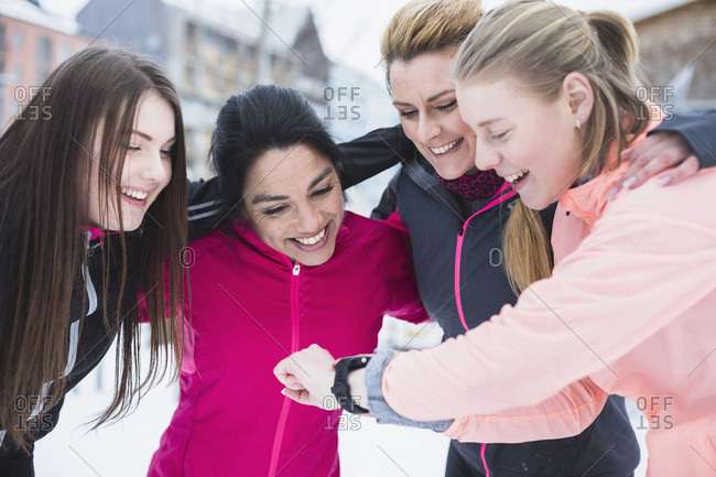 Young woman showing smart watch to female friends in winter