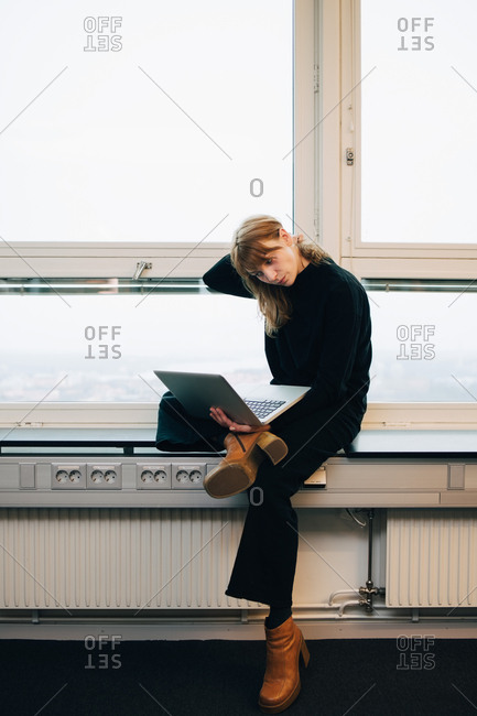 Full length of confident young businesswoman using laptop while sitting on window sill at creative office