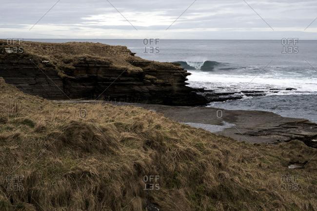 Waves breaking against headland on rocky coastline