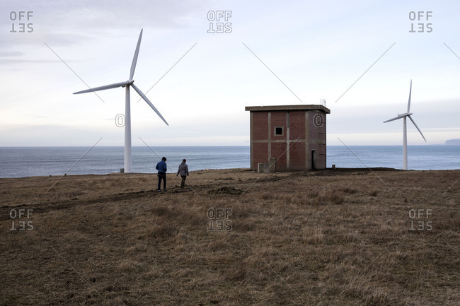Two people walking by large wind turbines along coast