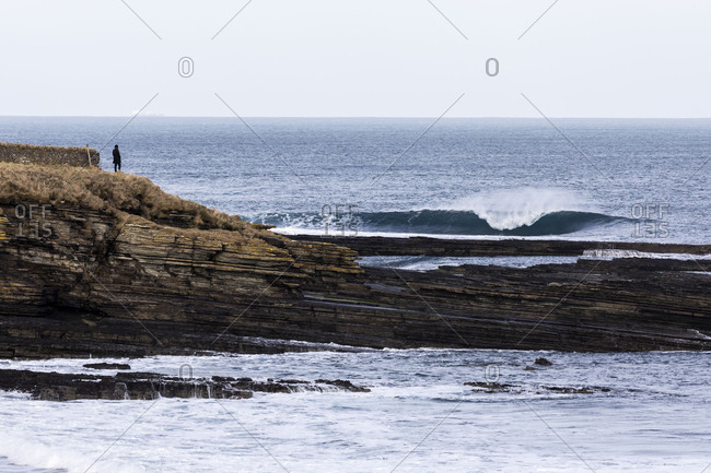 Person standing on edge of coastal cliff looking out at the ocean waves