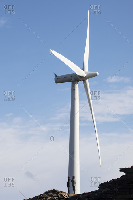 Two people standing at the base of a large wind turbine