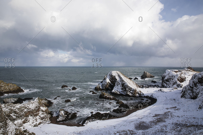Scenic view of snow covered rocky coastline
