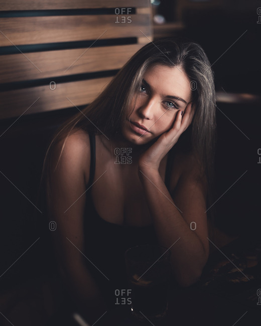 Attractive woman with bright glance in black shirt sitting in wooden room and looking at camera